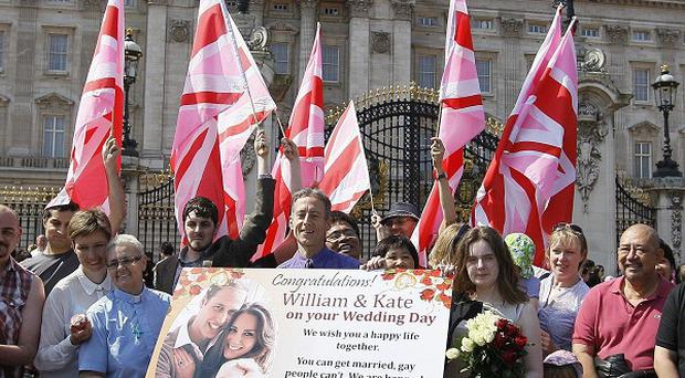 Gay rights activist Peter Tatchell, centre, holds a wedding card for Prince William and Kate Middleton (AP)