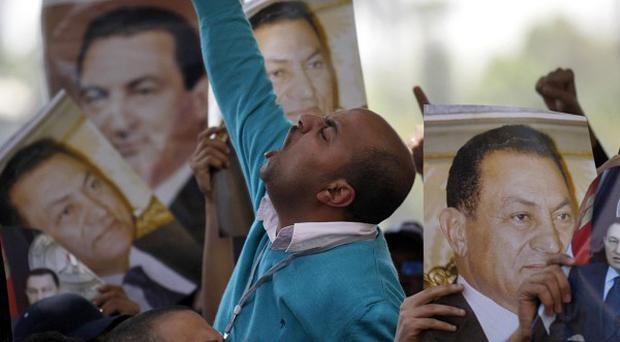 Egyptian protesters hold pictures of former Egyptian president Hosni Mubarak (AP)