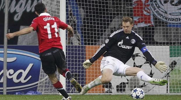 Manchester United's Ryan Giggs, left, scores against Schalke goalkeeper Manuel Neuer during the semi-final first leg Champions League soccer match in Gelsenkirchen, Germany