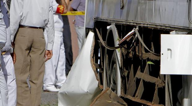 Pakistani Navy personnel examine a damaged bus at the site of a bomb blast in Karachi (AP)