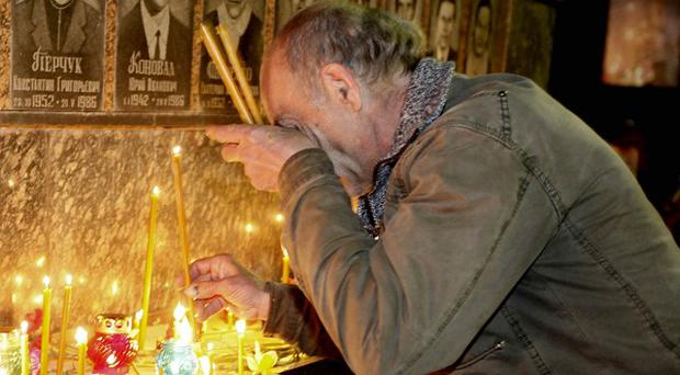 A Ukrainian lights candles to commemorate those who died after the Chernobyl nuclear disaster (AP)