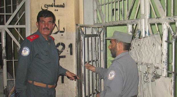 Taliban insurgents dug a tunnel underground into the main jail in Kandahar and more than 450 prisoners escaped (AP)