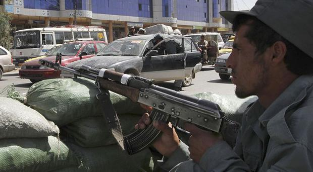An Afghan policeman at a checkpoint, as his colleagues check cars for the escaped Taliban insurgents in Kandahar (AP)