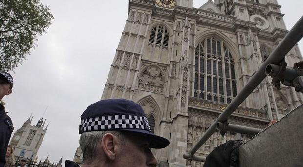 Police officers run through security preparations for the royal wedding outside Westminster Abbey (AP)