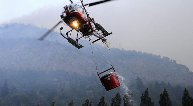 A helicopter carries water as smoke rises from a forest wildfire in Visp, southern Switzerland (AP)