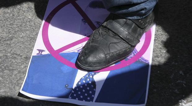 A Syrian protester symbolically steps on a picture of the Syrian president Bashar Assad during a protest in Amman, Jordan (AP)