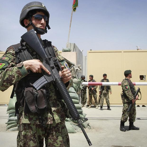 Afghan soldiers stand guard outside an airport gate in Kabul after an army officer opened fire, killing nine people (AP)