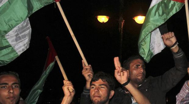 Palestinians wave flags in support of a reconciliation between the rival Fatah and Hamas movements in Gaza City (AP)