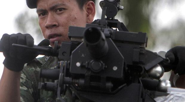 A Thai soldier stands on a military vehicle as he patrols amid clashes with Cambodian troops (AP)