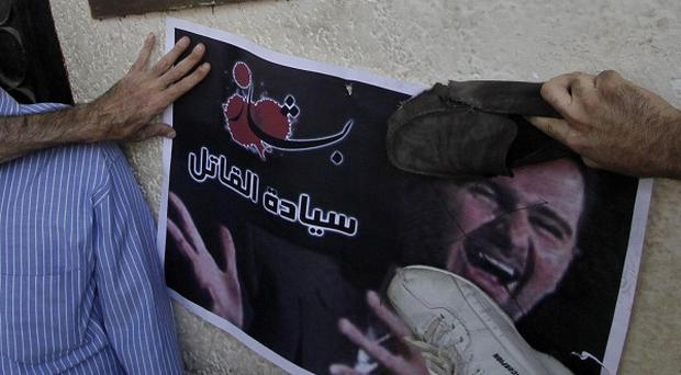 A Syrian protester kicks a poster of President Bashar Assad as hundreds of members quit the ruling Baath party
