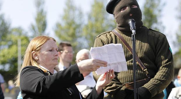 A member of the Real IRA reads a statement during a 1916 Easter Rising memorial at Cregan Cemetery in Londonderry