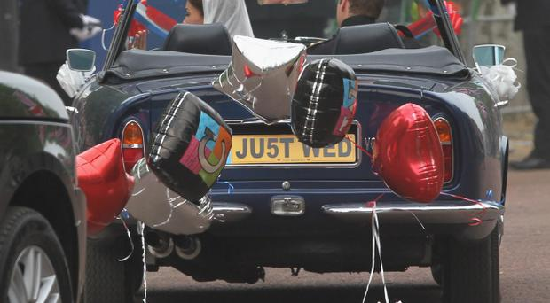 LONDON, ENGLAND - APRIL 29: Their Royal Highnesses Prince William, Duke of Cambridge and Catherine, Duchess of Cambridge drive from Buckingham Palace to Clarence House in an old convertible that had