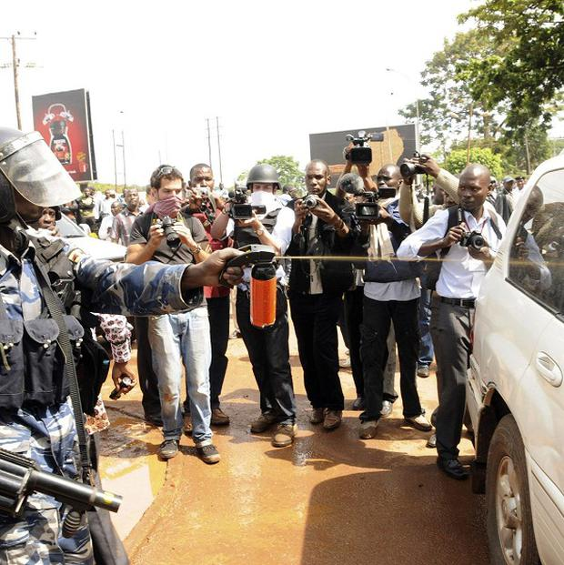 A Ugandan police officer douses opposition leader Dr Kizza Besigye with tear gas in his car before arresting him (AP)