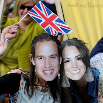 A couple wearing Prince William and Kate Middleton masks enjoy royal wedding celebrations in Manchester