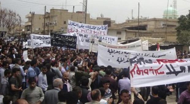 Syrian protesters carry banners calling for a democratic nation as they demonstrate in the north-eastern town of Qamishli (AP)