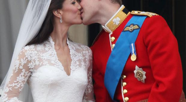 LONDON, ENGLAND - APRIL 29: Their Royal Highnesses Prince William, Duke of Cambridge and Catherine, Duchess of Cambridge kiss on the balcony at Buckingham Palace on April 29, 2011 in London, England. The marriage of the second in line to the British throne was led by the Archbishop of Canterbury and was attended by 1900 guests, including foreign Royal family members and heads of state. Thousands of well-wishers from around the world have also flocked to London to witness the spectacle and pageantry of the Royal Wedding. (Photo by Peter Macdiarmid/Getty Images)