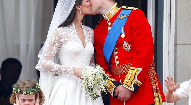 Prince William and his wife Kate Middleton kiss on the balcony of Buckingham Palace