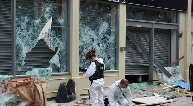 Police examine the scene outside a Tesco Express after a riot broke out in Bristol
