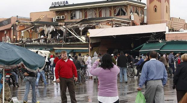 Tourists take pictures of a cafe destroyed in an explosion in Morocco