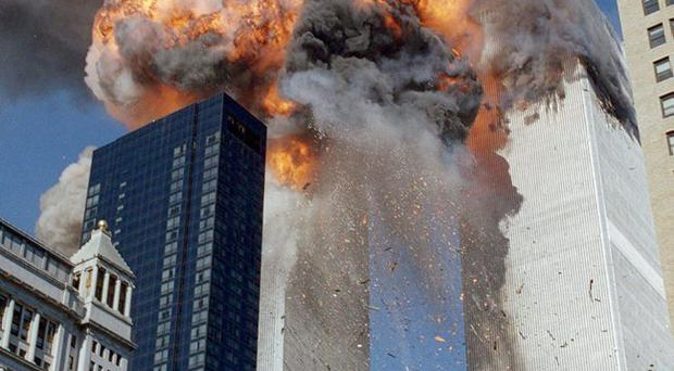 Smoke, flames and debris erupt from one of the World Trade Center towers after a plane strikes it, in New York.