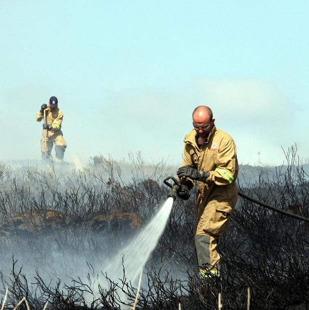 Firefighters try to contain a gorse fire in North Antrim, near Ballypatrick forest (PA)