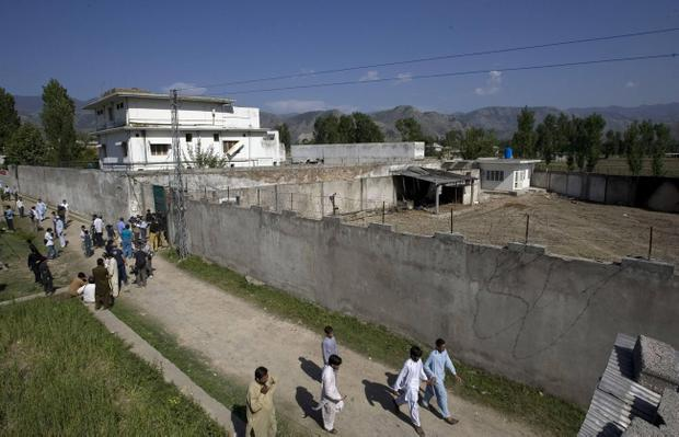 In this May 3, 2011, photo, media and local residents gather outside the house where al-Qaida leader Osama bin Laden was caught and killed, in Abbottabad, Pakistan. The nail-biting, 40-minute clandestine operation that resulted in Osama bin Laden's death could have been a calamitous political and military failure; a bloodbath in Pakistan that left U.S. forces and scores of civilians dead or captured by America's most ferocious enemy. (AP Photo/Anjum Naveed)