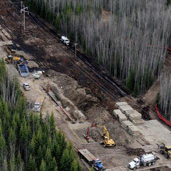 A broken section of a pipeline is worked on north-east of Peace River in Alberta (AP)
