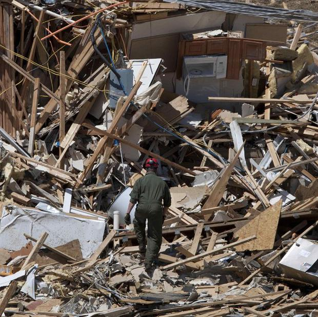 Tuscaloosa fire lieutenant Brian Phillips climbs a pile of rubble in search of survivors or bodies at an apartment building (AP)