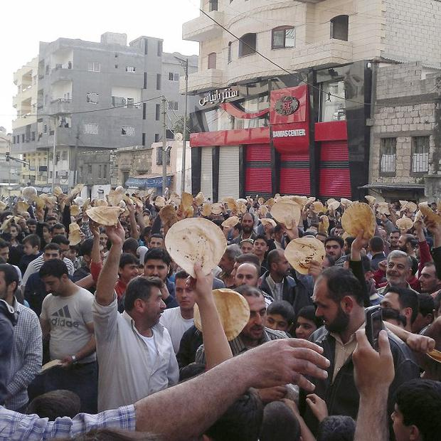 Syrian men carry bread loaves during a protest against President Bashar Assad's regime (AP)