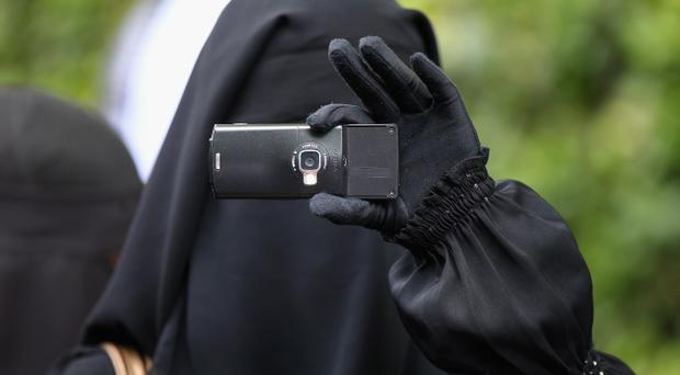 LONDON, ENGLAND - MAY 06: A Muslim woman films a protest against the killing of Osama bin Laden outside the US embassy in Mayfair on May 6, 2011 in London, England. The demonstration, which was called by radical Muslim cleric Anjem Choudary, was in close proximity to a rival protest by the English Defense League who were celebrating the death of the al-Queda leader. (Photo by Oli Scarff/Getty Images)