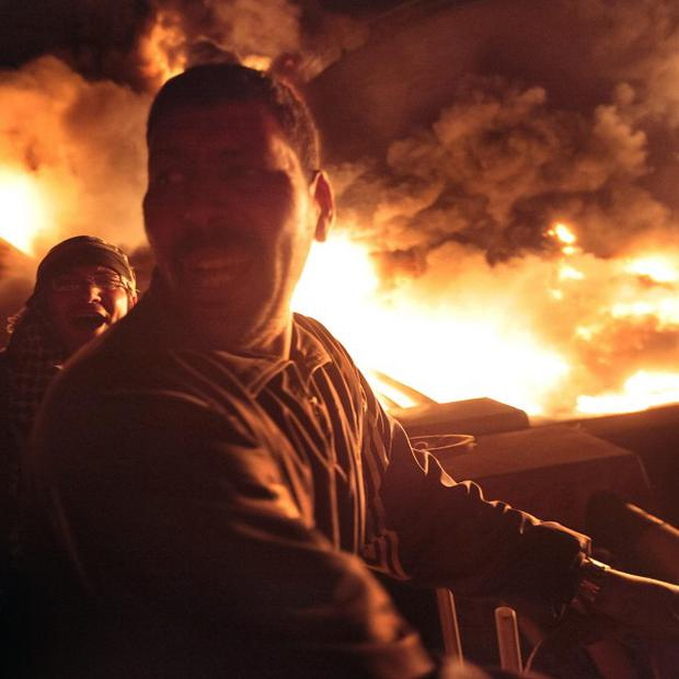 Libyan men react as the main fuel depot in Misrata burns after a bombing by pro-Gadhafi forces (AP)
