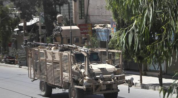 A Nato military vehicle crosses the empty street after gunmen launched an attack on the compound of the provincial governor in Kandahar, south of Kabul, Afghanistan (AP)