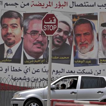 A car passes a pro-government billboard in Bahrain which shows pictures of jailed opposition leaders (AP)