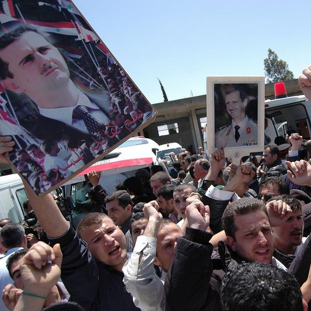 Supporters of Syrian President Bashar Assad during a funeral for soldiers and security force members (AP/SANA)