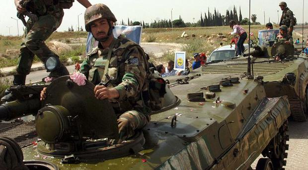 Syrian soldiers on armored vehicles pull out of the southern city of Daraa, Syria