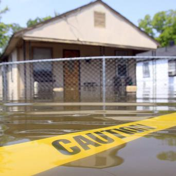 Caution tape floats in floodwater surrounding a home in Memphis, Tennessee (AP)
