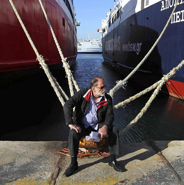 A man sits in front of moored ships in Piraeus port near Athens during a 24-hour strike (AP)