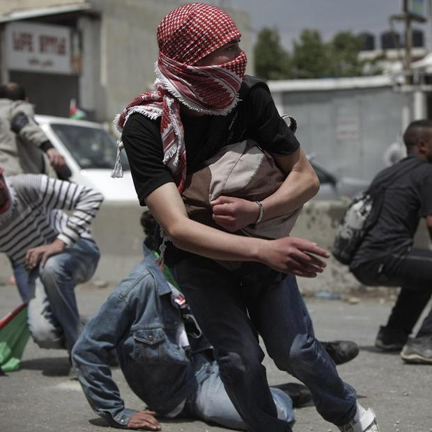 Palestinian protesters run from tear gas fired by Israeli soldiers near the Qalandiya checkpoint between the West Bank city of Ramallah and Jerusalem (AP)