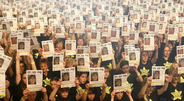 Around 10,000 members of the Rock Choir hold up posters showing pictures of missing children at Wembley Arena