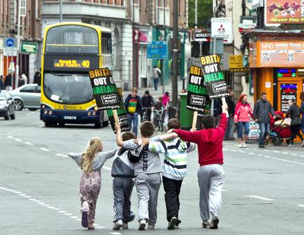 Local youngsters having some fun with spare placards after a protest by eirigi in Parnell Square, Dublin