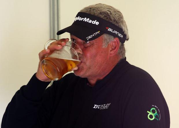 Thirsty work: Darren Clarke enjoys a pint after yesterday's final round as he watches his challengers who are still out on the course
