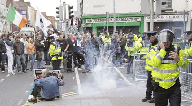A firework goes off as protestors are stopped by Garda in a street in Dublin, after the Queen Elizabeth arrived in the country for a four day state visit.