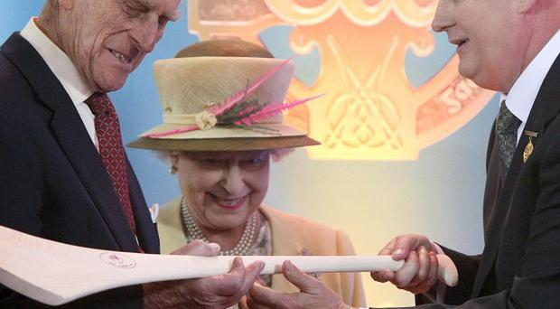 The Queen and the Duke of Edinburgh admire a hurley passed to them by GAA President Christy Cooney