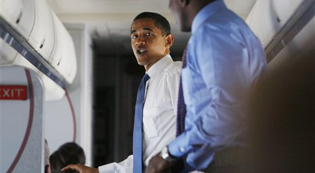 President Obama speaks with aide Reggie Love while on his plane