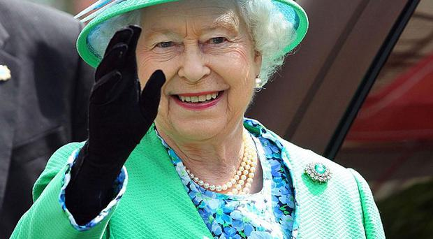 Queen Elizabeth waves goodbye to the people of Cork at the English Market in Cork City on her state visit to Ireland