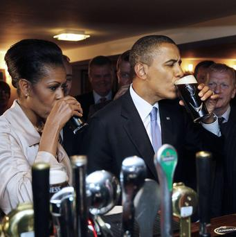 US President Barack Obama and first lady Michelle Obama drink Guinness as they meet local residents at Ollie Hayes pub in Moneygall (AP)