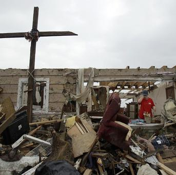 A woman pauses as she picks through the rubble of her mother's home in Joplin after a large tornado struck (AP)