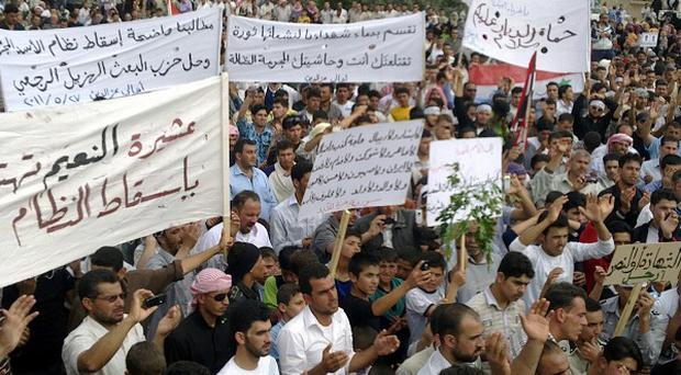 Syrian anti-regime protesters carry banners during a rally in Talbiseh, in the central province of Homs, Syria
