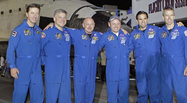 The crew of space shuttle Endeavour pose for a photo after landing at the Kennedy Space Centre (AP)