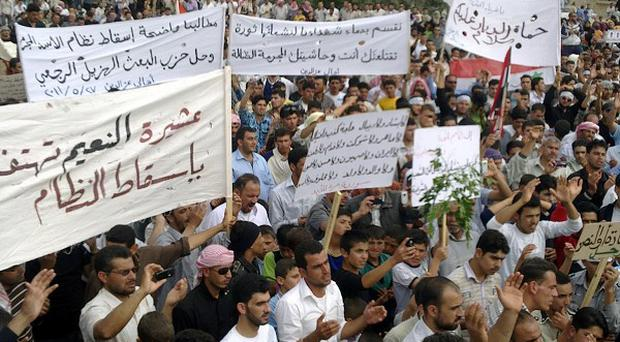 Syrian anti-regime protesters carry banners during a rally in Talbiseh, in the central province of Homs (AP)